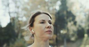 特写镜头投入在耳朵无线耳机的健身女孩 听到音乐的女运动员妇女赛跑者佩带的airpods 股票录像