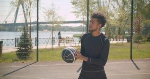 特写镜头投掷球的年轻英俊的非裔美国人的男性篮球运动员侧视图画象入箍 影视素材