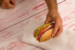 特写镜头拿着三明治的一个人 图库摄影