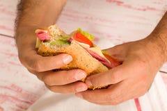 特写镜头拿着三明治的一个人 库存照片