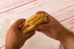 特写镜头拿着三明治的一个人 免版税图库摄影