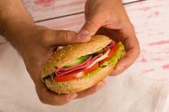 特写镜头拿着三明治的一个人 免版税库存照片