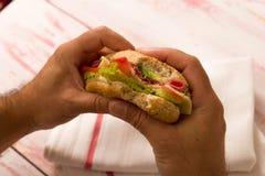 特写镜头拿着三明治的一个人 免版税库存图片