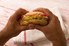特写镜头拿着三明治的一个人 库存图片