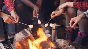特写镜头拿着棍子用在火焰和游人`腿上的蛋白软糖的射击了灼烧的营火和人` s手 股票录像