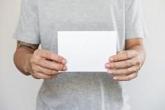 特写镜头拿着空白的白皮书的一个人 免版税图库摄影