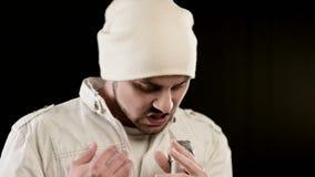 特写镜头挂名负责人歌唱者与一个时髦的胡子的岩石流行音乐在白色衣裳和一个帽子有一个话筒的在他的手上 股票视频
