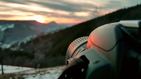 特写镜头捉住日落的照相机集合 冬天风景、橙色天空和日落在背景中 库存照片