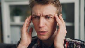 特写镜头接触他的头的被射击不健康的人由于偏头痛按摩寺庙户内 病的年轻人 股票视频