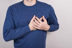 特写镜头握在胸口的不快乐的害怕人播种的看法照片画象手佩带蓝色套头衫被隔绝的灰色 免版税库存图片