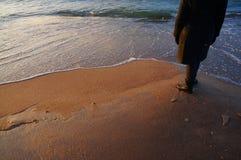 特写镜头旅行妇女走的脚和腿在与海波浪的海滩在日落在冬天 库存照片