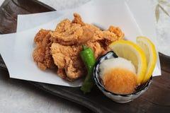 特写镜头日语油炸了与烹调纸的Karaage服务与天麸罗调味汁Tentsuyu混合剁碎萝卜的鸡 库存照片