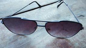 特写镜头时尚太阳镜有木背景 库存照片