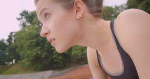 特写镜头是幼小白种人运动的母的慢跑者侧视图画象在长凳的被用尽的休息的开会在都市 影视素材