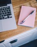 特写镜头有笔和膝上型计算机谎言的桃红色笔记本在一张木桌上 库存图片
