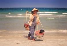 特写镜头有轭的老妇人供营商在海洋海滩站立 免版税库存图片