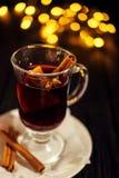 特写镜头杯加香料的热葡萄酒用桔子和桂香在深黑色背景,在白色板材,圣诞灯,大黄色 库存图片