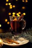特写镜头杯加香料的热葡萄酒用桔子和桂香在白色板材,圣诞灯 免版税库存图片