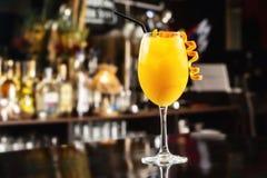 特写镜头杯在酒吧柜台后面的橙色螺丝刀鸡尾酒 免版税库存图片