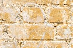 特写镜头构造了以黄色绘的一块多彩多姿的砖的背景 在一块老打破的砖的极热的黄色油漆 免版税库存照片