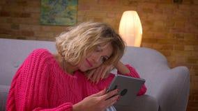 特写镜头桃红色毛线衣的愉快的主妇观看入片剂的被射击满意地对舒适家庭环境 影视素材