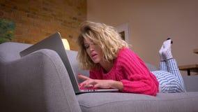 特写镜头桃红色毛线衣的白肤金发的主妇说谎在沙发的胃键入在舒适家庭环境的膝上型计算机的被射击  股票视频
