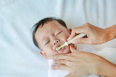 特写镜头母亲手干净的乳齿和舌头有软的橡皮擦的 免版税图库摄影