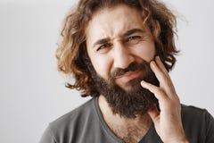 特写镜头水平的射击与卷发感人的胡子的东部男性和皱眉从反感,表达 免版税库存照片