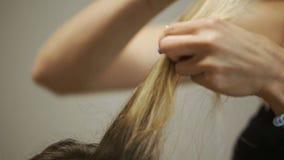 特写镜头沙龙Naches在白肤金发的簪子的电烫发型 影视素材
