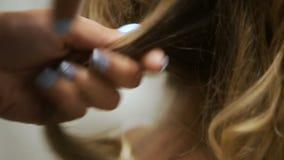 特写镜头沙龙Naches在白肤金发的簪子的电烫发型 股票录像