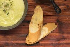 特写镜头浓豌豆汤用在土气木桌,顶视图上的面包 免版税图库摄影