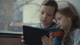 特写镜头游遍乘公共汽车的射击了一个年轻男孩和女孩城市,观看在计算机片剂的电影 影视素材