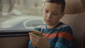 特写镜头游遍乘公共汽车的射击了一个年轻男孩城市 他使用在他的智能手机的社会网络和听 股票视频