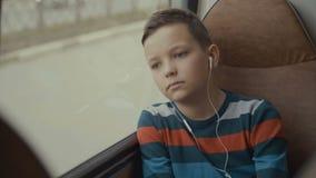 特写镜头游遍乘公共汽车的射击了一个年轻男孩城市 他听到音乐 股票视频
