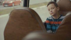 特写镜头游遍乘公共汽车的射击了一个年轻男孩城市 他听到音乐 影视素材