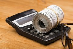 特写镜头滚动了与计算器ang玻璃的美国美元钞票 库存图片