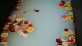 特写镜头热水澡用牛奶,柑橘切,并且玫瑰花瓣 影视素材