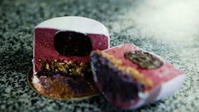 特写镜头焦点在切成两半的紫色给上釉的奶油甜点微型蛋糕 股票录像