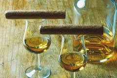 特写镜头照片两雪茄、一个瓶酒精和一块两块玻璃  免版税库存照片