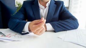 特写镜头照片年轻商人摩擦手指和请求贿款 库存照片