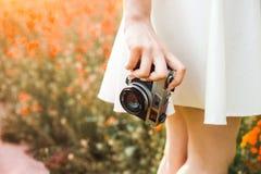 特写镜头照片,手拿着在一块colorized花田、概念的创造性和自已的背景的模式胶卷相机 免版税库存照片