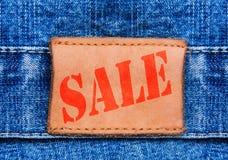 特写镜头牛仔裤与文本销售额的皮革标签 图库摄影