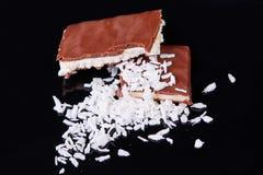 特写镜头牛奶巧克力用椰子在黑背景切削 自创椰子巧克力片 库存图片