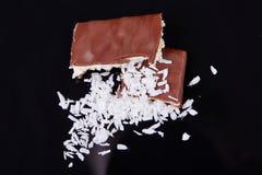 特写镜头牛奶巧克力用椰子在黑背景切削 自创椰子巧克力片 图库摄影