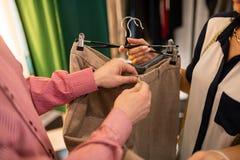 特写镜头男性检查米黄裤子服装辅助部件  免版税库存图片