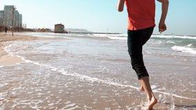 特写镜头男性腿沿海滨夏天海滩运行 查出的黑色概念自由 低角度侧视图 享受假期的人 4K 影视素材