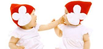 特写镜头画象两在面对面红色的帽子的婴孩孪生 免版税库存照片