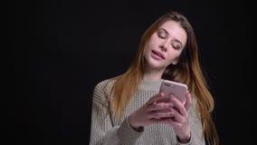 特写镜头画象使用电话的年轻美丽的白种人女性和微笑在照相机前面 股票视频