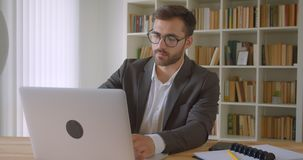 特写镜头画象在玻璃的成人英俊的白种人商人使用膝上型计算机和松劲满意地 股票视频