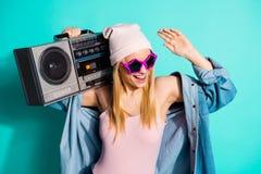 特写镜头画象她她运载立体声MP3播放器的好可爱的可爱的逗人喜爱的快乐的爽快高兴的正面女孩 库存图片